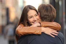stock photo of hug  - Portrait of a happy couple hugging in the street with the woman face in foreground - JPG