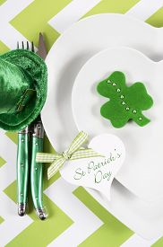 picture of chevron  - Happy St Patricks Day table place setting with heart shape plates shamrock cookie and leprechaun hat on green and white chevron stripe table vertical - JPG