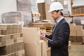 foto of warehouse  - Serious warehouse manager checking inventory in warehouse - JPG