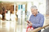 picture of mall  - Senior Man In Shopping Mall Using Mobile Phone - JPG