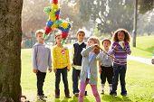 foto of pinata  - Children Hitting Pinata At Birthday Party - JPG