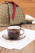 pic of private investigator  - Coffee cup paper sheets and detective hat on old Wooden table - JPG