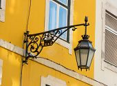 image of wrought iron  - Traditional black wrought iron wall lantern on a yellow wall - JPG