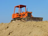 stock photo of grub  - old orange bulldozer stops waiting for work - JPG