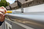 foto of gutter  - Close Up Of Man Replacing Guttering On Exterior Of House - JPG