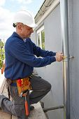 stock photo of gutter  - Workman Replacing Guttering On Exterior Of House - JPG