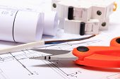 foto of electrical engineering  - Cable cutter electric wire and fuse rolls of electrical diagrams lying on construction drawing of house accessories for engineer jobs - JPG
