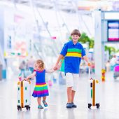 pic of brother sister  - Two children traveling by airplane at Dusseldorf International airport laughing teenager boy and a toddler girl brother and sister holding colorful luggage ready to fly for summer beach vacation - JPG