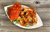 picture of cooked crab  - High angled view of freshly cooked crab with spicy sauce and herbs on white serving plate - JPG