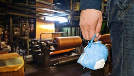 picture of respirator  - Worker with protective respirator at man hands at industrial factory - JPG