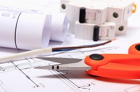 stock photo of wire cutter  - Cable cutter electric wire and fuse rolls of electrical diagrams lying on construction drawing of house accessories for engineer jobs - JPG