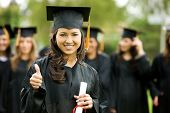 picture of graduation gown  - graduation girl holding her diploma with pride - JPG