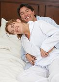 Beautiful couples portrait playing on the bed
