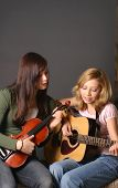 picture of musical instrument string  - two teenage sisters with violin and guitar against dark background - JPG