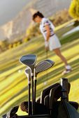 picture of golf bag  - Bag of golf clubs outdoors and a player on the background - JPG