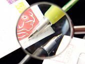 Two Pens Under An Stamped Envelop Close-Up With The Magnifying Glass