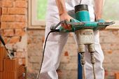 image of grout  - Construction worker mixing concrete or grout with a hand mixer - JPG