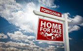 Red Foreclosure Home For Sale Real Estate Sign Over Beautiful Clouds and Blue Sky.