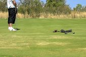 picture of wet pants  - Golfer standing on the green with two golf clubs in his hand - JPG
