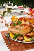 stock photo of turkey dinner  - Feasting backed turkey on holiday table ready to eat - JPG
