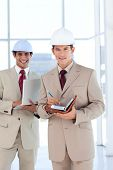 Portrait of two architects wearing hard hat smiling at the camera