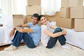 Feliz pareja relajarse sentados en el suelo mientras se mueve de casa