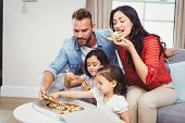 Family of four eating pizza while sitting on sofa at home poster