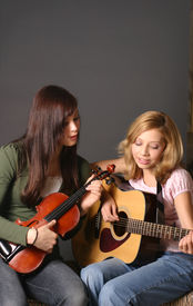 pic of musical instrument string  - two teenage sisters with violin and guitar against dark background - JPG