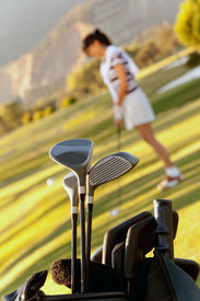 pic of golf bag  - Bag of golf clubs outdoors and a player on the background - JPG