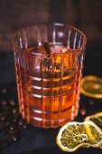 An Ice Cube Floats In Alcohol In A Glass. A Glass With Whiskey On A Wooden Background. Close-up Of A poster