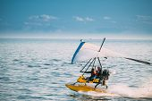 Motorized Hang Glider With Muslim Woman Take Off Frow Sea In Sunny Summer Day. Muslim People Having  poster