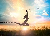 Freedom Concept: Silhouette Of A Woman Jumping And Broken Chains At Orange Meadow Sunset With Her Ha poster