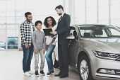 African American Family At Car Dealership. Salesman Is Signing Papers For New Grey Car. poster