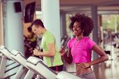 young people exercisinng a cardio on treadmill running machine in modern gym poster