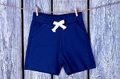 Clothesline With Hanging Kids Shorts. Childs Blue Shorts Drying On Rope On Grey Wooden Background. poster