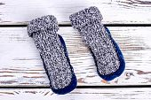 Two Woolen Knitted Socks. Warm Winter Socks With Velour Soles On White Wooden Background. Shop New C poster