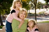 Twin Girls With Grandmother Laughing In The Park