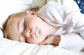 Cute Adorable Baby Girl Of 6 Months Sleeping Peaceful In Bed At Home. Closeup Of Beautiful Peaceful  poster