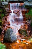 Water Cascading Over Red Algae Covered Rocks