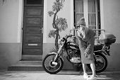 Woman Biker At Bike Transport. Parisian Fashion Model Near House And Motorcycle. Look And Retro Styl poster