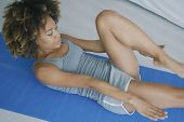 From above shot of young fit ethnic model lying on mat at home and training abdominal muscles doing  poster