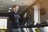 Young Man With Smartphone Before Running On Treadmill In Gym. Fitness Guy Jogging In Fitness Club, L poster