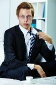 Portrait of tired businessman untying necktie
