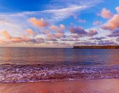 Beautiful Colorful Sunrise At The Sea With Dramatic Pink Clouds Over Blue Sky And Soft Waves. Beauty poster