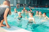 Female instructor teaches children how to swim. Kids with goggles in water listening trainer. Happy  poster