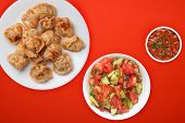 Dumplings On A White Plate Against A Red Background. Dumplings Meat In Tomato Sauce With Vegetable S poster