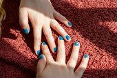Vibrant Blue Painted Fingernails Criss Crossed On A Red Background poster
