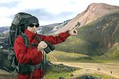 Traveler With Backpack Red Jacket With Binoculars In Hand On The Slopes Of Mount Points Into The Dis poster