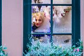 A Young Blonde Woman Looks Through A Window Pane That Is Frozen And Adorned With Christmas Decoratio poster