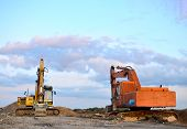 Two Excavators At A Construction Site. Excavator With Crusher Bucket For Crushing Concrete. Construc poster
